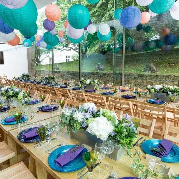 woodplank tables and folding chair dining with colourful crockery and glassware