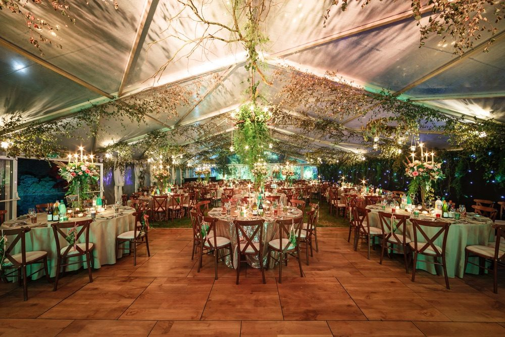 party planned for Cotswolds tables ready for dining in a marquee - cross-back chairs and lavish foliage for a party planning Oxfordshire