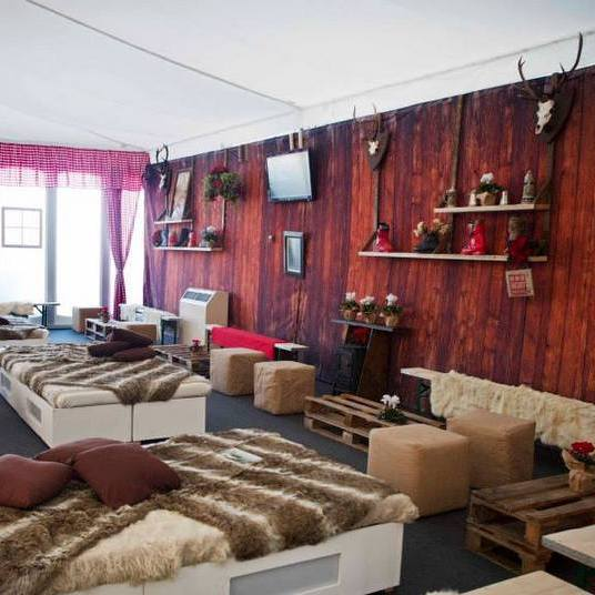 Printed fabrics for bespoke finishes in a marquee - woodplank walling with animal fur chillout furniture
