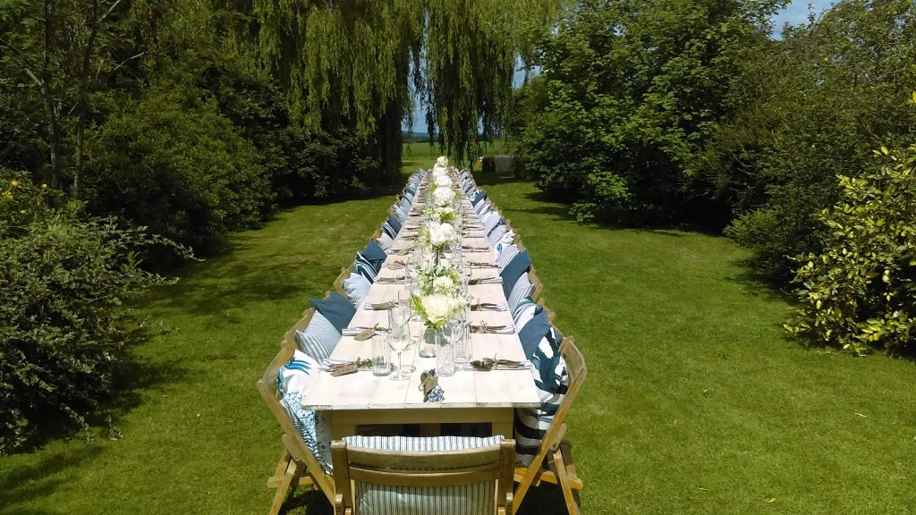 A Summer lunch setting with wooden trestle tables