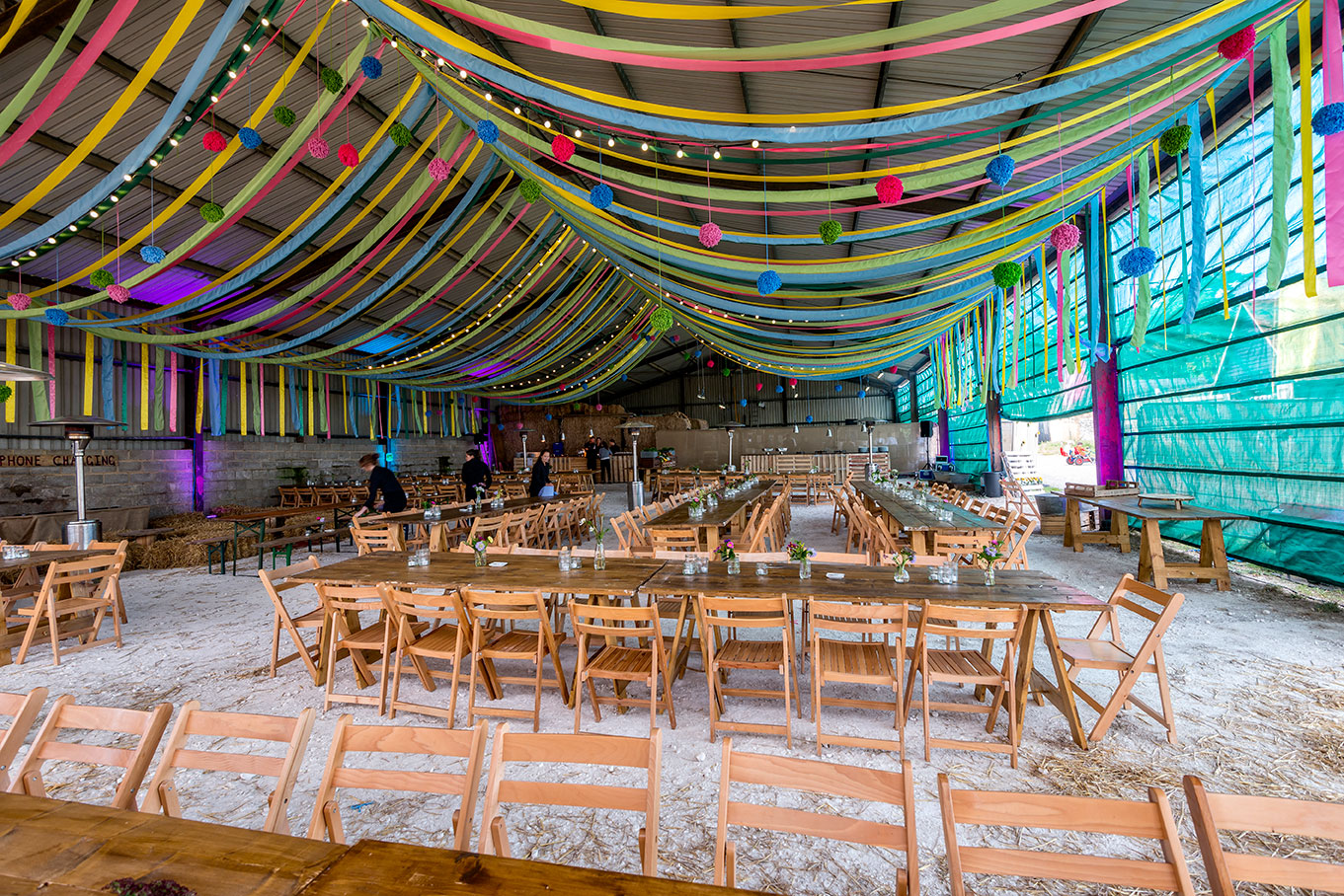 Transformed tractor barn with ribbon canopy for family festival dining