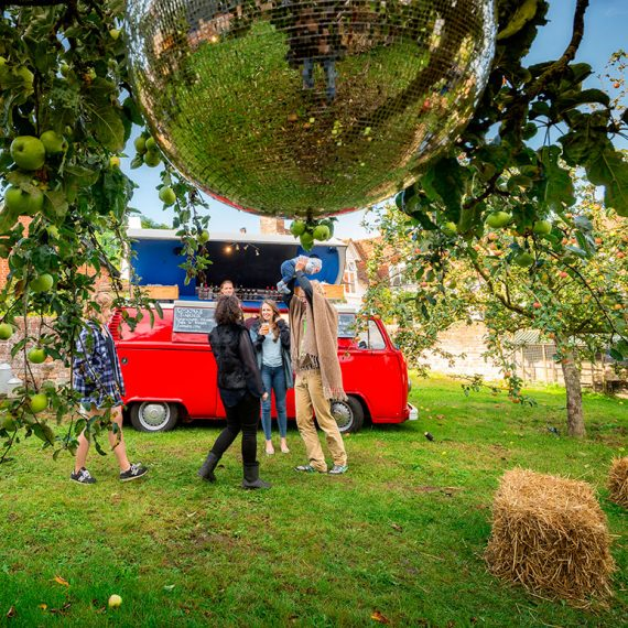A cocktail camper van serving in the mirror ball filled orchard