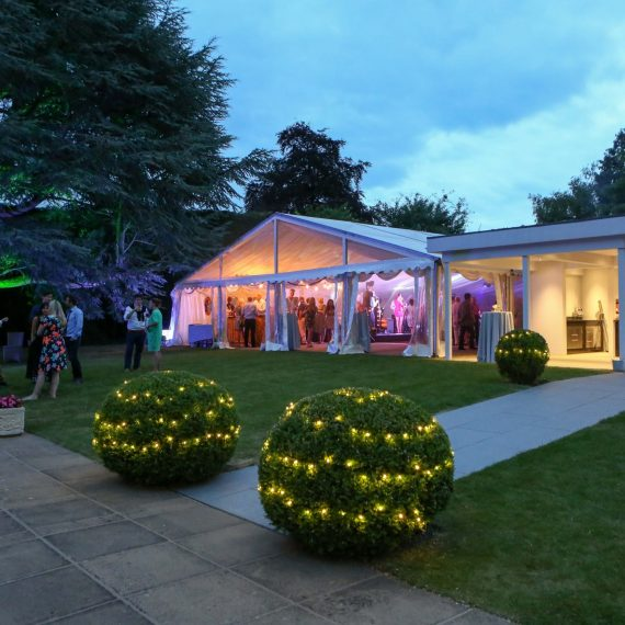 Marquee joined to house with garden lighting